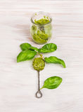 Basil pesto in glas with old spoon Royalty Free Stock Image