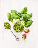 Basil pesto in glass jar with spoon,fresh leaves and tomatoes Stock Images