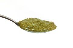 Basil pesto pn a teaspoon. Basil pesto on a teaspoon on a white background Stock Photography