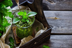 Basil pesto sauce in glass on wooden table. Royalty Free Stock Image