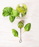 Basil pesto in vintage spoon and glass with fresh herbs leaves Stock Photos