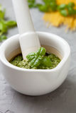 Basil pesto in a white mortar Stock Photo