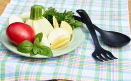 Basil, pomidor, zucchini, inni świezi ogrodowi ziele na talerzu na stole z w kratkę tkaniną z kuchennym materiałem i vegs, i obraz stock