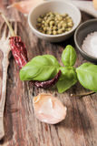 Basil with salt and pepper balgarskih, garlic. On a wooden background royalty free stock image