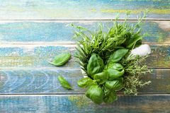 Basil, thyme, rosemary and tarragon. Aromatic herbs in mortar bowl on rustic wooden table top view. Fresh ingredients for cooking. Stock Image