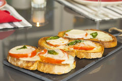 Basil tomato and cheese bruschetta over a slate rock board Stock Images