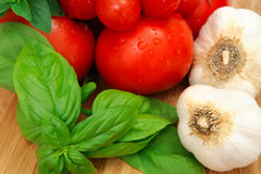 Basil And Tomatoes. Fresh herbs and vegetables to make spaghetti sauce, including tomatoes, basil, oregano and garlic Stock Photo