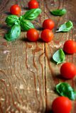 Basil and tomatoes. Fresh leaves of basil placed with cherry tomatoes on wooden background Stock Photo
