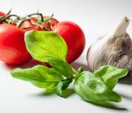 Basil tomatoes and garlic on white background Stock Photo