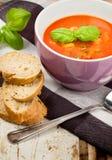 Basilic et pain frais savoureux de soupe à tomate Photographie stock