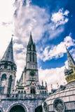 Basilica della nostra signora del rosario contro il bello cielo Lourdes, Francia, Hautes Pirenei Fotografie Stock Libere da Diritti