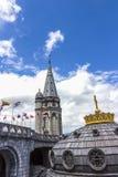 Basilica della nostra signora del rosario e delle bandiere dei paesi differenti contro il cielo blu Lourdes, Francia Immagini Stock