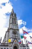 Basilica della nostra signora del rosario e delle bandiere dei paesi differenti contro il cielo Lourdes, Francia, Hautes Pirenei Fotografia Stock