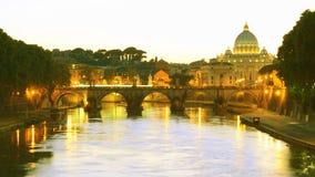 Basilica di San Pietro over Sant Angelo bridge on Tevere river at dusk. Basilica of San Pietro overlooking the Tevere river and surrounding historical landmarks Stock Photos
