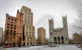 Basilica of Notre-Dame of Montreal and Place d`Armes on snow - Montreal, Quebec, Canada royalty free stock photos