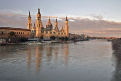 Basilica of Our Lady of the Pillar at  sunrise. Basilica–Cathedral of Our Lady of the Pillar reflecting in waters of Ebro river in early morning in  lights Royalty Free Stock Photo