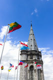 The Basilica of our Lady of the Rosary and flags of different countries against the blue sky. Lourdes, France, Hautes Stock Photos