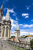 Basilica of our Lady of the Rosary and flags of different countries against the sky. Lourdes, France, Hautes Pyrenees Royalty Free Stock Photography