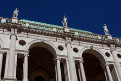 Basilica Palladiana arches and statues with blue sky. Wonderful Basilica Palladiana marble arches and statues 16th-17th century in Vicenza with blue sky royalty free stock photos