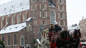 Basilica of Saint Mary. KRAKOW, POLAND - DECEMBER 2017; Carriage with horses in front of the Basilica of Saint Mary stock footage