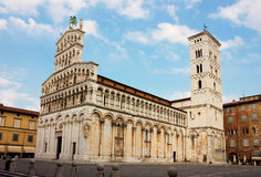 Basilica San Michele in Foro in Lucca, Italy. Basilica San Michele in Foro with the famous statue of Madonna salutis portus at the corner of the facade in Lucca Royalty Free Stock Image