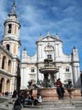 The Basilica of the Sanctuary of the Holy House of Loreto in Ita. The facade of the Basilica of the Sanctuary of Loreto, the bell tower and the fountain. Marche stock photography