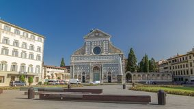 Basilica of Santa Maria Novella in the homonym square timelapse hyperlapse in Florence. Flowerbeds and green grass. People sitting on a bench. Blue sky at stock video footage