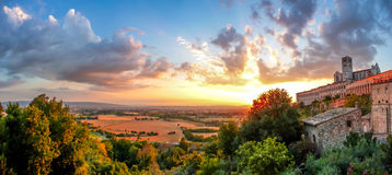 Basilica of St. Francis of Assisi at sunset, Umbria, Italy. Famous Basilica of St. Francis of Assisi (Basilica Papale di San Francesco) and golden harvest fields Royalty Free Stock Image