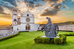 Basilica of St. Francis of Assisi at sunset, Umbria, Italy. Famous Basilica of St. Francis of Assisi (Basilica Papale di San Francesco) with statue at sunset in Royalty Free Stock Image