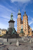 Basilica of Virgin Mary and Adam Mickiewicz Statue. The basilica of the Virgin Mary, brick Gothic church re-built in the 14th century (originally built in the royalty free stock images