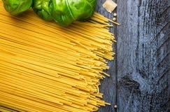 Basilicumbladeren en ruwe spaghetti op blauwe houten achtergrond, hoogste mening Stock Afbeeldingen