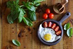 Basilika, kryddor, tomater och en stekpanna med ett ägg på tabellen royaltyfri fotografi