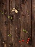 basilikaleaSlices av limefrukt, andves för körsbärsröda tomater på ett trä arkivbild