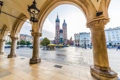 Basilikan för St Mary ` s, shoppar och byggnader på Rynek Glowny i Krak arkivfoton
