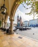 Basilikan för St Mary ` s, shoppar och byggnader på Rynek Glowny i Krak arkivfoto