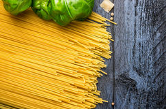 Basilikumblätter und rohe Spaghettis auf blauem hölzernem Hintergrund, Draufsicht Stockbilder