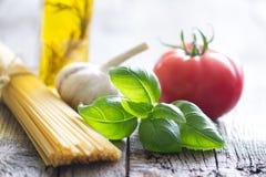 Basilu czosnku i pomidoru jedzenia wciąż włoski życie z makaronem na retro deskach Zdjęcie Royalty Free