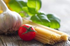 Basilu czosnku i pomidoru jedzenia wciąż włoski życie z makaronem na retro deskach Zdjęcie Stock