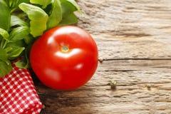 Basilu pomidor na drewnie i liście Fotografia Stock