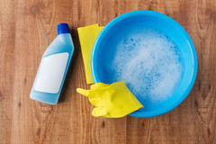 Basin with cleaning stuff on wooden background Royalty Free Stock Photography