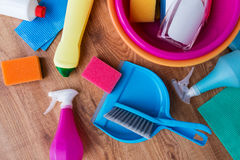 Basin with cleaning stuff on wooden floor Stock Images