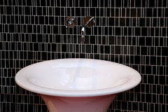 Basin detail. Small ceramic oval basin in bathroom with decorative tiles Royalty Free Stock Photography