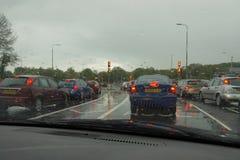 BASINGSTOKE, Großbritannien, am 25. Mai 2016: Der Verkehr, der als die Lichter ansteht, ändert an einem stumpfen, regnerischen Ab Stockbild