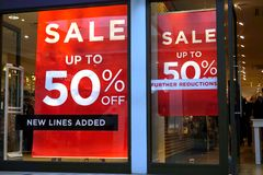 Basingstoke, UK - January 04 2017: Shop fronts of UK fashion stores with 50% off Sale signs royalty free stock photos