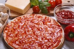 Basis for pizza with tomato sauce and ingredients Royalty Free Stock Image