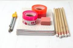 Basiskantoorbehoeften - notitieboekjes, potloden, banden, kompas, gom stock afbeelding