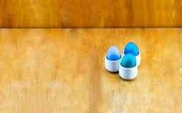 Basissamenstelling van drie blauwe eieren in ceramische onderleggers voor glazen op houten Stock Afbeeldingen