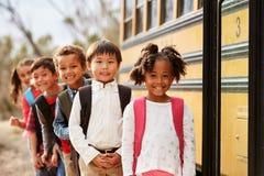 Basisschooljonge geitjes die op een schoolbus een rij vormen te krijgen Stock Foto's