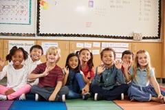 Basisschooljonge geitjes die op klaslokaalvloer zitten stock foto's