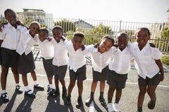 Basisschooljonge geitjes in het stellen van Afrika in schoolspeelplaats stock afbeeldingen